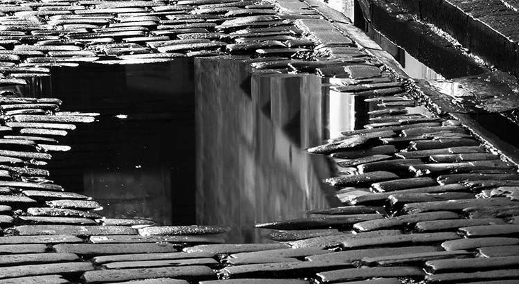 Puddle on dark cobbled street at night. Used with permission from byronv2 via flickr.